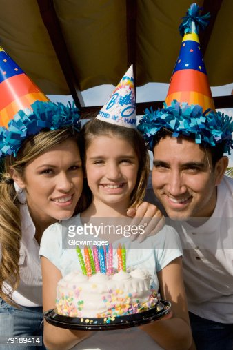 Portrait of a girl with her parents holding a birthday cake and smiling : Foto de stock