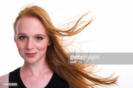 Portrait of a girl with moving red hair and freckles