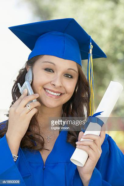 Portrait of a Graduate Holding a Scroll and Making a Call on Her Mobile Phone