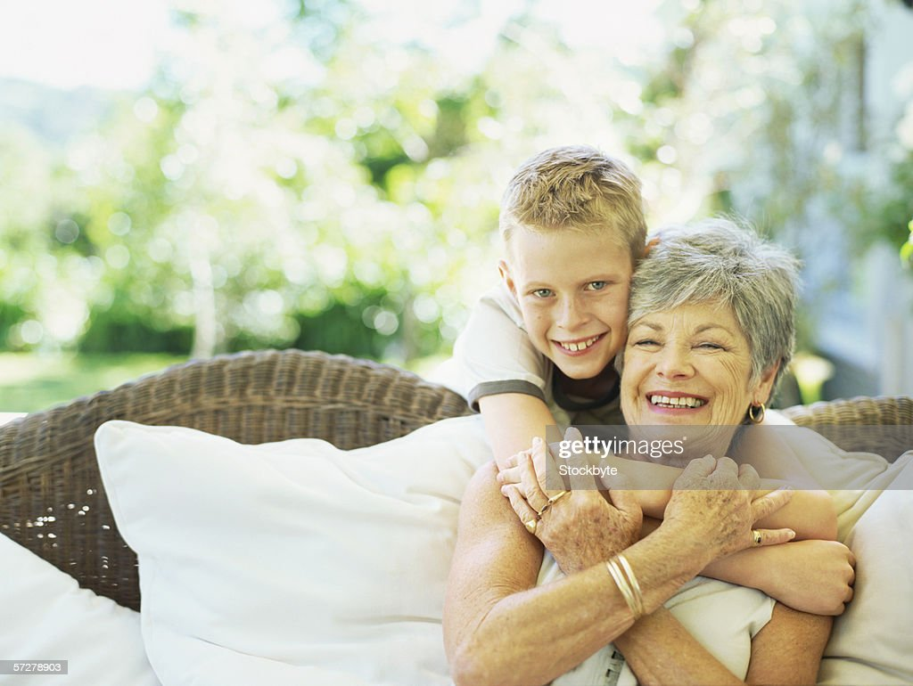 Portrait of a grandson hugging his grandmother : Stock Photo