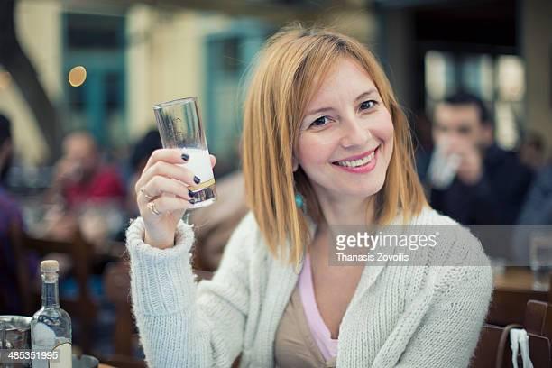 Portrait of a greek woman drinking ouzo