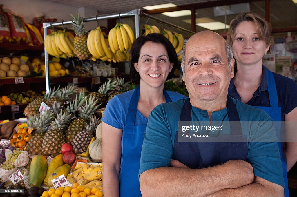 Portrait of a grocer with his team : Stock Photo