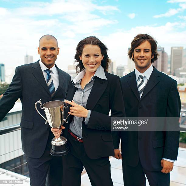 portrait of a group of business executives standing holding a trophy cup