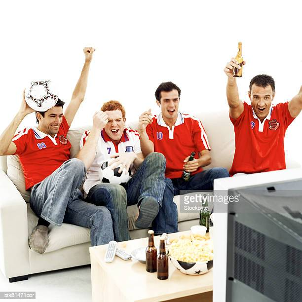 portrait of a group of football fans sitting on a couch and watching the game