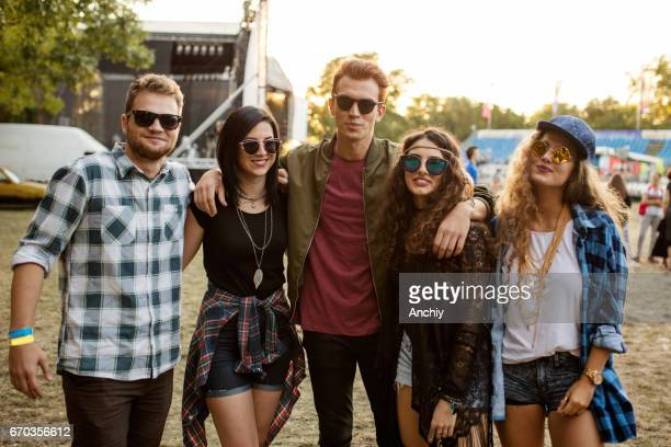 Portrait of a group of people that are embraced and standing at the festival area