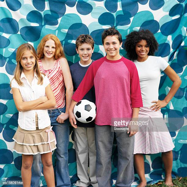 portrait of a group of teenagers standing smiling