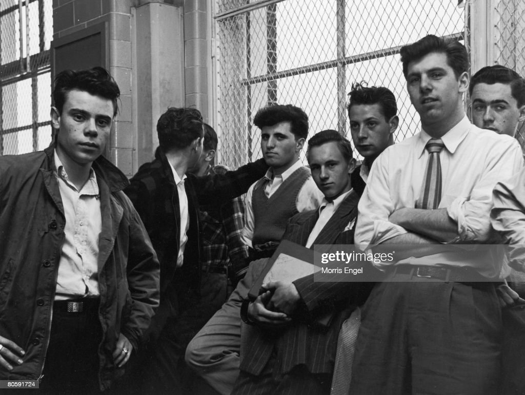 Portrait of a group of unidentiifed high school students as they lean against a wire mesh-covered window in a school hallway, New York, New York, late 1940s.