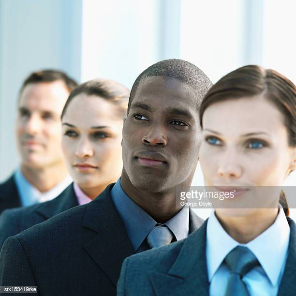 Portrait of a group of young business executives standing one behind the other looking sideways
