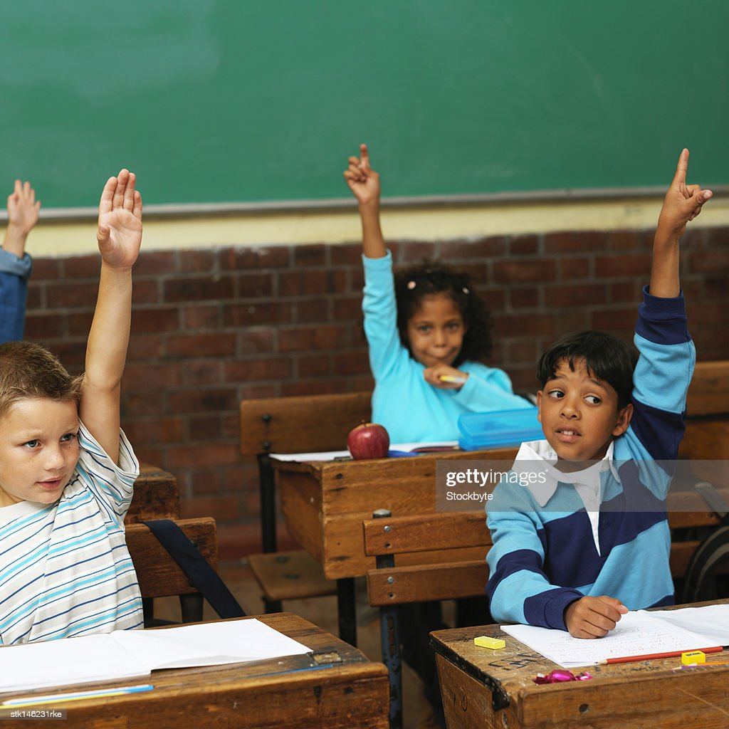 portrait of a group of young students raising their hands up to answer in class : Stock Photo