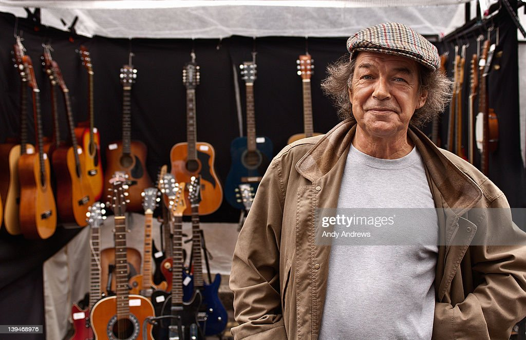 Portrait of a guitar seller in front of his stall : Stock Photo