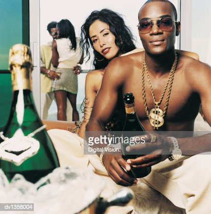 Portrait of a Half Dressed Young Man Holding a Champagne Bottle Sitting With a Woman With a Couple Against a Railing in the Background : Stock Photo