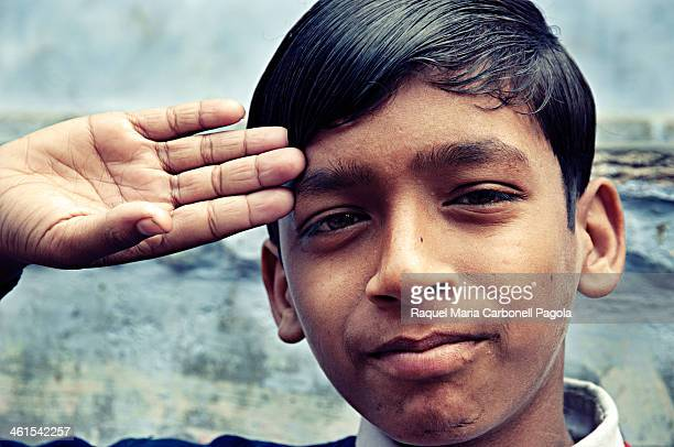 Portrait of a handsome schoolboy doing the military salute