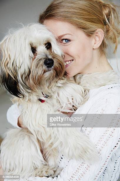 portrait of a happy adult woman cuddling her dog