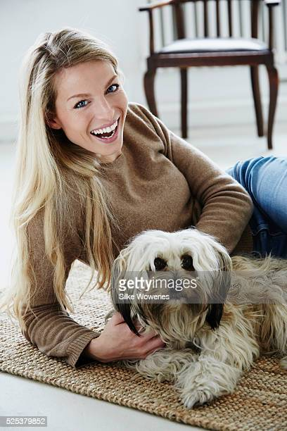 portrait of a happy adult woman laying on the floor cuddling her dog