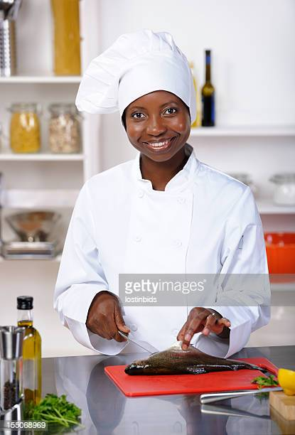 Portrait Of A Happy African American Female Chef Preparing Fish