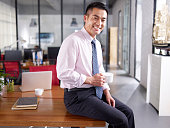 an asian businessman holding cup of coffee sitting on desk in office, smiling and cheerful.