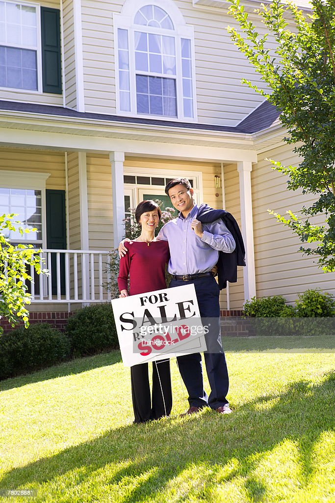 Portrait of a happy couple standing in front of the home they just purchased