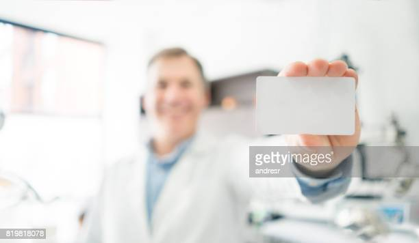 Portrait of a happy dentist holding a business card