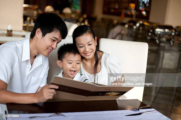 Portrait of a happy family looking through a menu