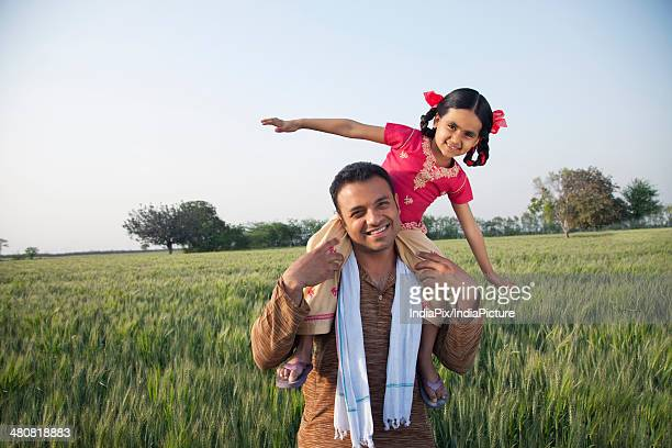 Portrait of a happy farmer carrying daughter on shoulders at farm against sky