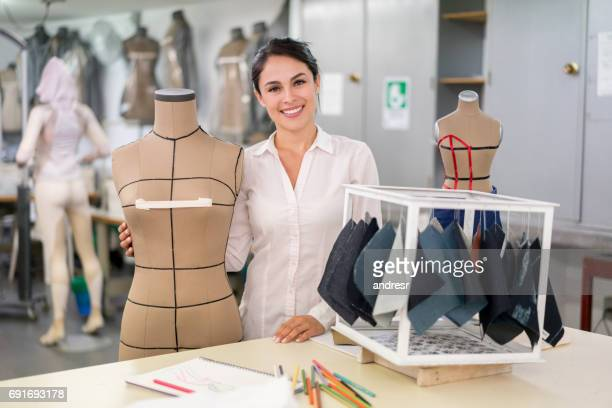 Portrait of a happy fashion designer at her atelier