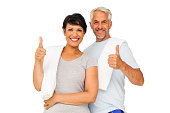 Portrait of a happy fit couple gesturing thumbs up over white background