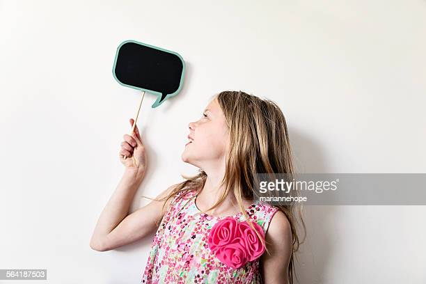 Portrait of a happy girl holding a blank thought bubble board above her head
