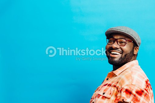 Portrait of a happy man in orange shirt looking up : Stock Photo