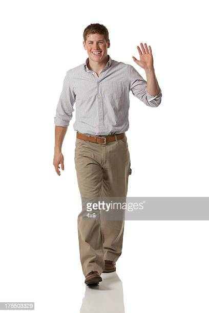 Portrait of a happy man walking and waving his hand