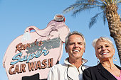 Portrait of a happy mature couple in front of car wash signboard