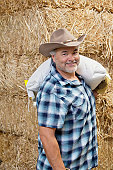 Portrait of a happy mature cowboy carrying sack on shoulder