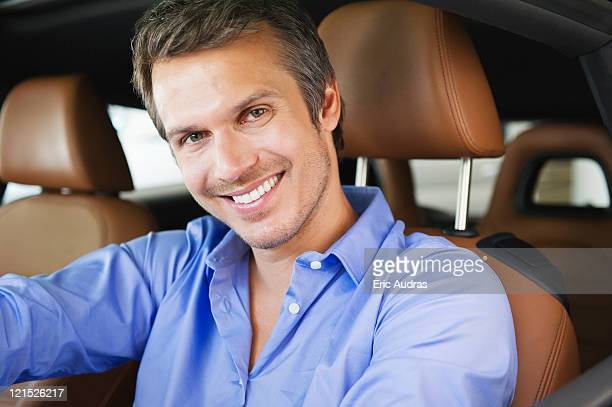 Portrait of a happy mid adult man taking a test drive