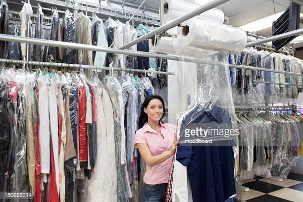 Portrait of a happy mid adult woman putting plastic to dry cleaned clothes in laundry