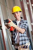 Portrait of a happy mid adult woman worker drilling at construction site