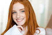 Portrait of a happy redhead woman in bathrobe looking at camera