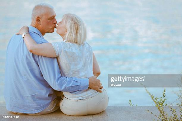 Portrait of a happy senior couple embracing and kissing at the waterfront