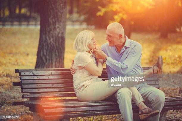 Portrait of a happy senior couple embracing and kissing on the park bench at sunset