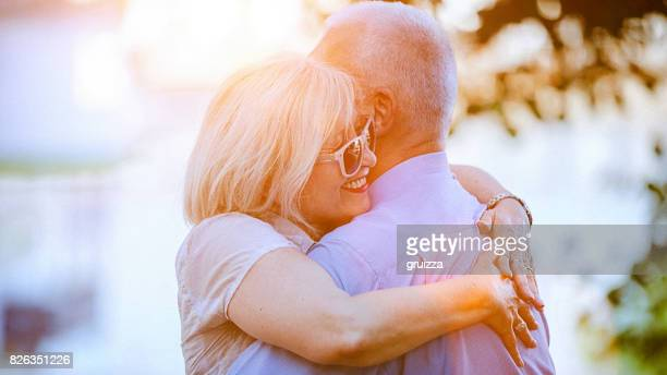 Portrait of a happy senior couple embracing and kissing outdoors