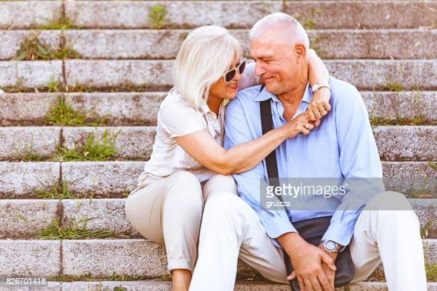 Portrait of a happy senior couple embracing and kissing while sitting on the stone stairs