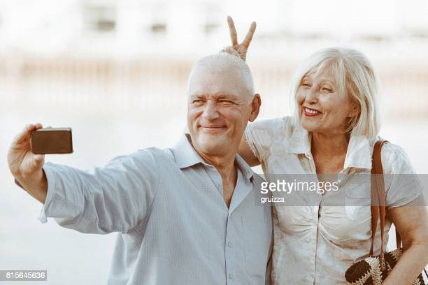Portrait of a happy senior couple making selfie with a smartphone at the waterfront