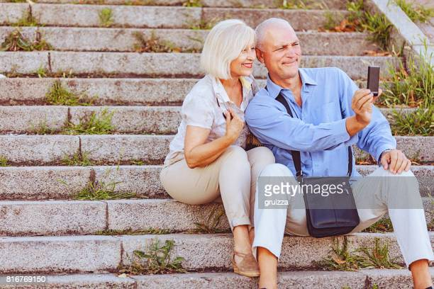 Portrait of a happy senior couple making selfie with a smartphone while sitting at the stone stairs