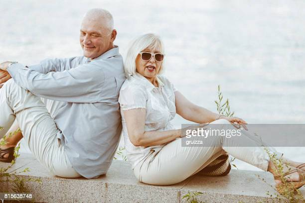 Portrait of a happy senior couple sitting back to back at the waterfront