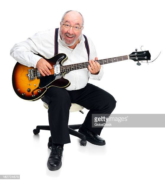 Portrait of a happy senior man playing guitar against white