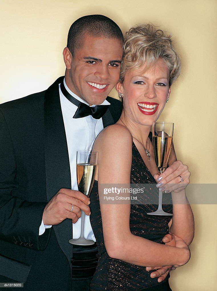 Portrait of a Happy Well-dressed Couple Holding Glasses of Champagne : Stock Photo