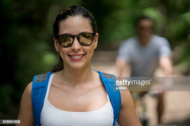 Portrait of a happy woman hiking and wearing her sunglasses