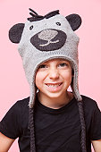 Portrait of a happy young boy wearing monkey cap over pink background