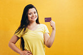 Portrait of a happy young girl showing plastic credit card isolated over yellow background