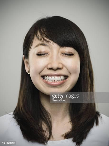 Ritratto di felice giovane donna guardando fotocamera giapponese