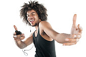 Portrait of a happy young man in vest dancing to tunes of mp3 player over white background