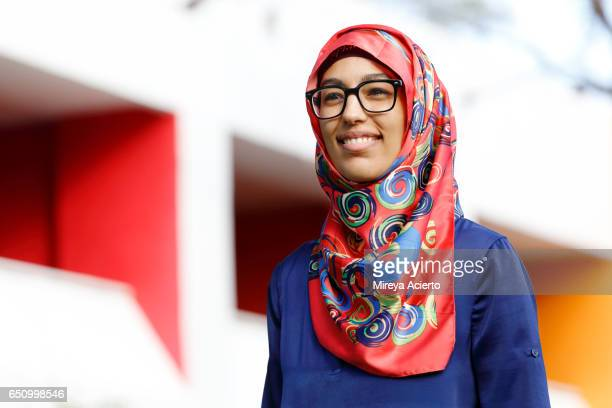 A portrait of a happy, young Muslim woman outside